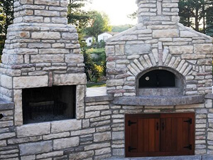 Forno Bravo fireplace kit next to a wood fired oven