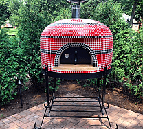 Napolino60 wood fired pizza oven by Forno Bravo shown on black powder coated steel stand with thermometer door in place. Black and Red tile finish with bushes in the background on patio..