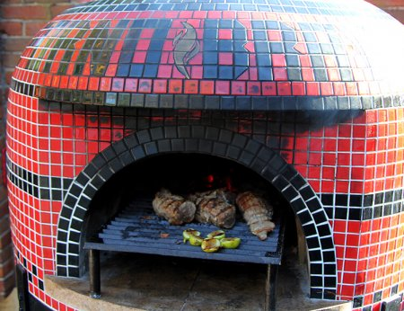 Napolino wood fired pizza oven by Forno Bravo cooking grilled pork tenderloin and figs. Oven is shown with custom tile and tuscan grill.