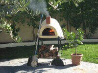 Primavera Outdoor Pizza Oven on Patio with Fire