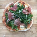 Cooked pizza with Pizza with Prosciutto and Arugula and Shaved Parmagian Cheese