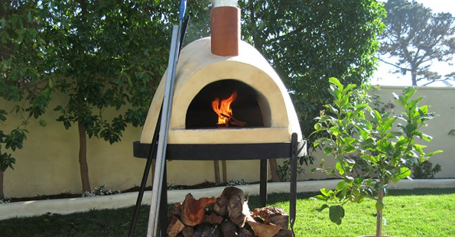 Primavera wood fired pizza oven shown in yard with fire in the dome and wood stacked on stand by Forno Bravo.