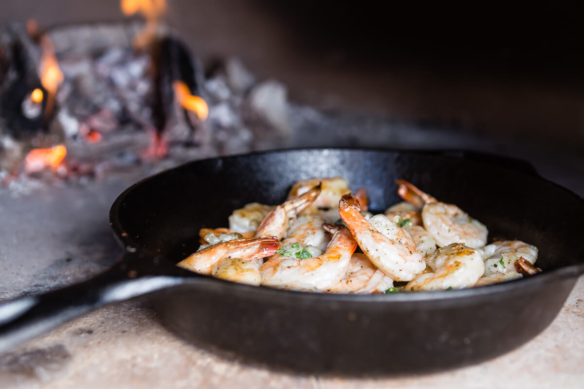 Shrimp cooking in a cast iron pan in a wood fired oven
