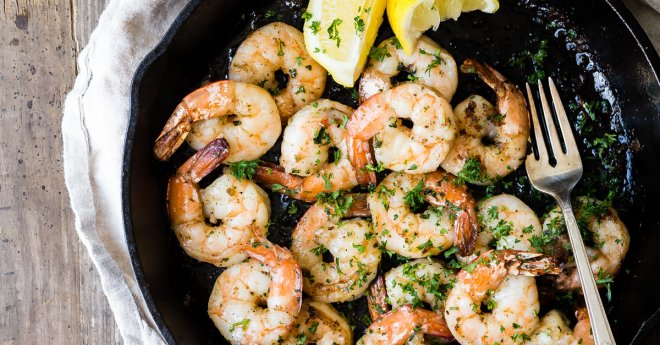 Cooked Shrimp in a Cast Iron Pan with Basil, Lemons and a Glass of White Wine