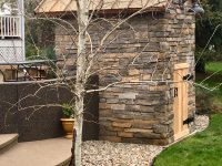 View of Side and Rear of a Casa110 Pizza Oven in the Craftsman Style - Stone Enclosure - Copper Roof - Cedar Door - Aspen Tree in Foreground