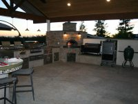 Covered, Open Air Putdoor Kitchen Anchored with a Casa110 Pizza Oven in the Corner with a Fire Burning at Sunset