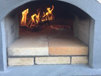 Front of Casa90 pizza oven with wood fire and pizza inside