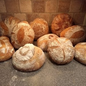 Pile of Round Loaves of Wood Fired Sourdough Bread on a Counter against a Brick Back Splash