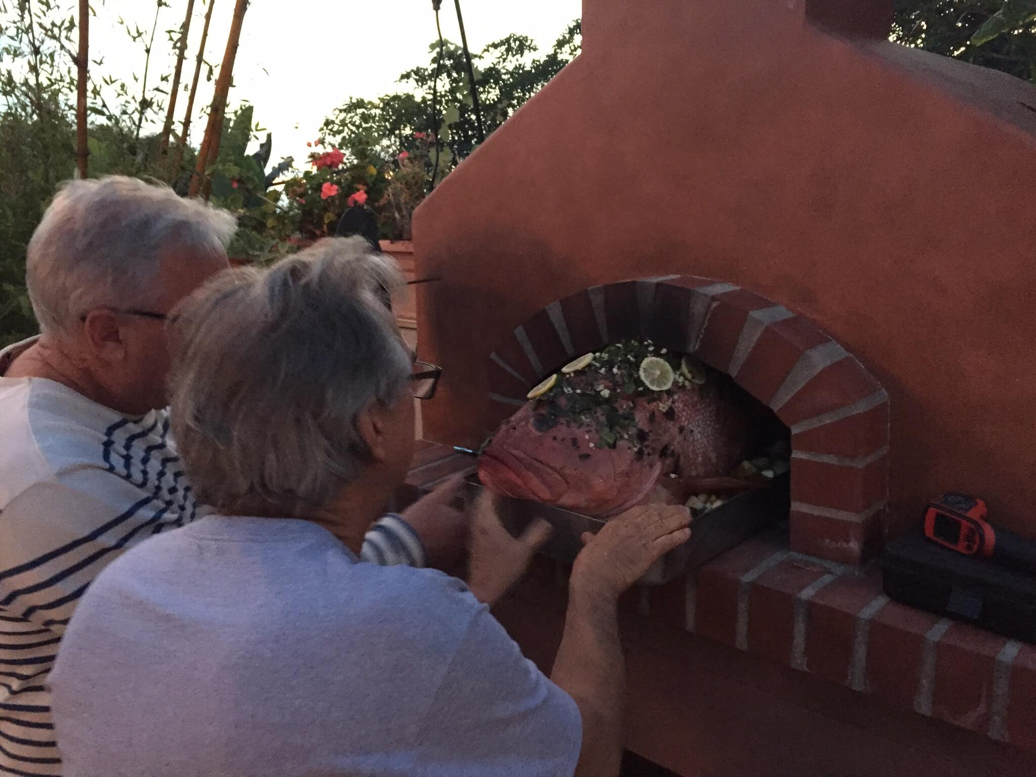 Two men easing a 28lb Pink Grouper into a Toscana pizza oven with zero inches to spare