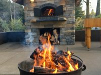 Black Metal Firepit in Foreground - Stone Enclosed Casa 110 Pizza Oven with Fire Burning and Metal Doors Open in the Background