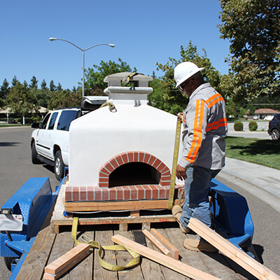 Toscana Oven on Trailer - Man in Safety Vest and hard hat