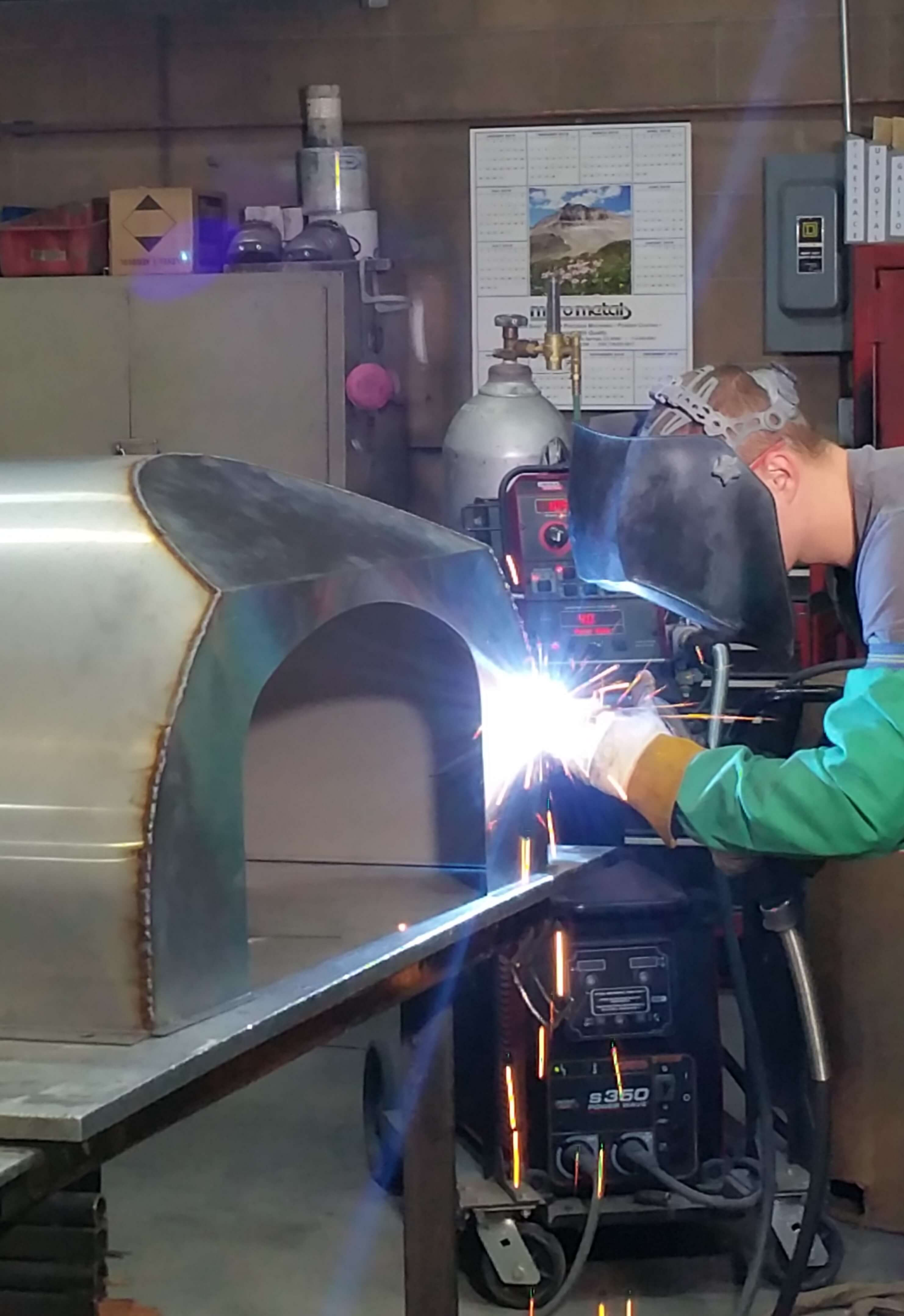 man welding Bell Pizza Oven