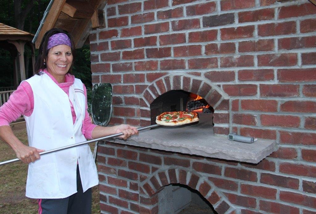 Woman in front of brick oven