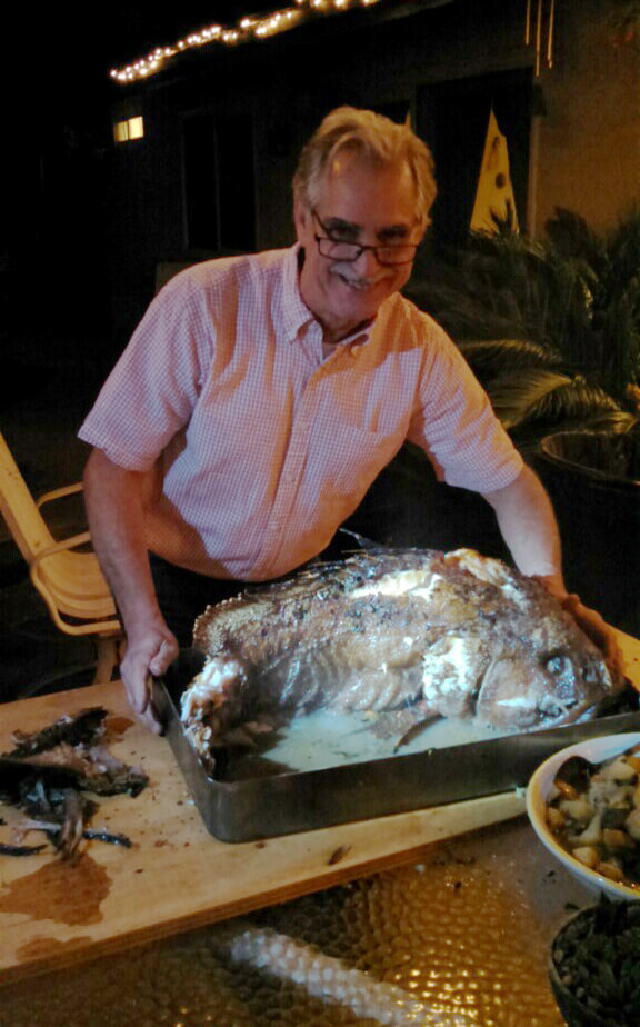 Man in pink shirt with large cooked fish