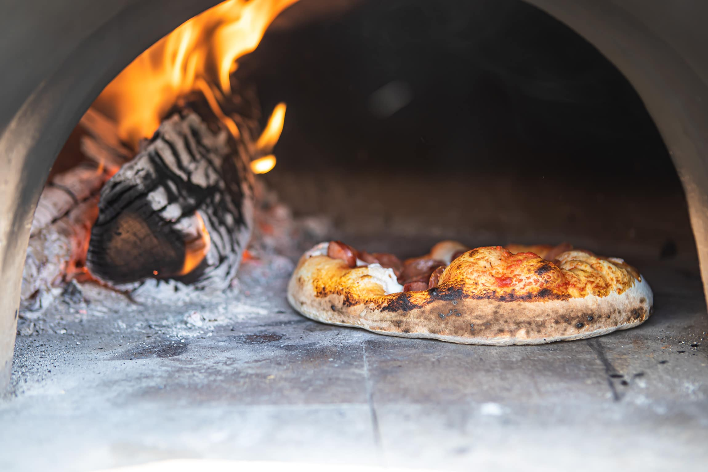 pizza baking in wood fired oven